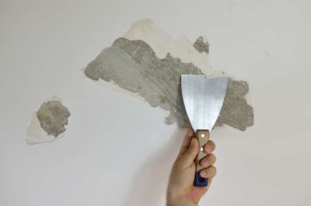 Hand holding a plaster spatula, peeling a ceiling, preparing it for smoothing 스톡 콘텐츠