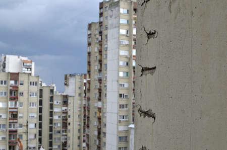 earthquake crack: Damaged concrete wall with visible iron construction of a skyscraper and buildings of that very kind in background Stock Photo
