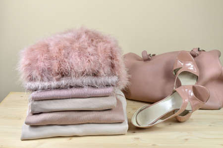 closet: Pile of different pink garments with elegant pink sandals and a bag beside it - on wooden shelf