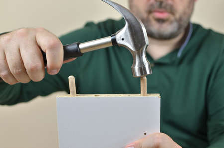 Man hammering wooden dowels in to a particle board of a new piece of furniture