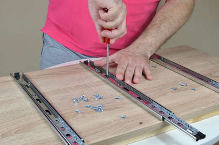 Man installing rails with a screwdriver on an element of a cabinet at home