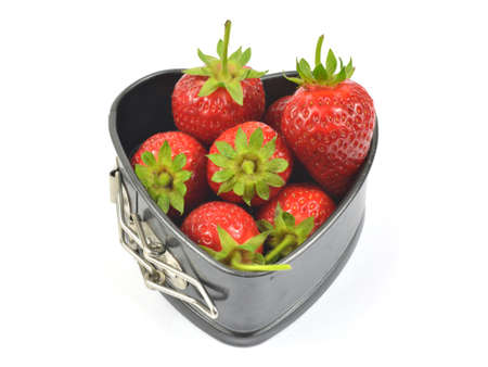 white backing: Fresh strawberries in a backing heart shaped souffle pan on white background