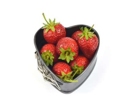 white backing: Strawberries in a backing heart shaped souffle pan on white background Stock Photo