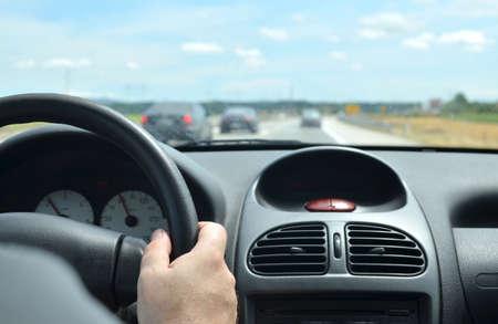 adentro y afuera: Hombre conduciendo un automóvil con un vidrio delantero sucio después de un largo viaje en una carretera con otros vehículos borrosos delante de él Foto de archivo