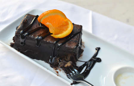 Rich chocolate cake with a fresh slice of orange - on white porcelain plate
