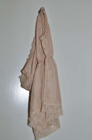 Silk night dress hanged on a wooden white door Banco de Imagens - 88684065