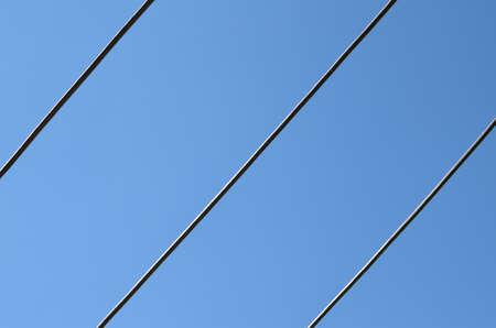 Diagonal iron bars against clear blue sky
