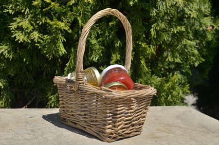 Small basket with small jars with jam for breakfast shot outdoor
