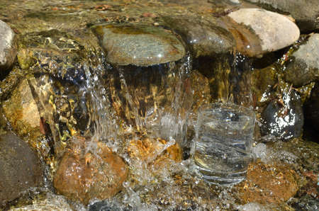 Glass of pure water in a fast flow of a stream