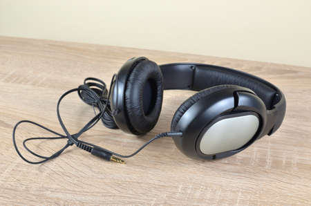 New black headphones with a cable set on a wooden desk