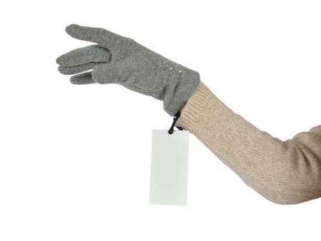 Womans hand in a grey woolen glove with a price tag on white background