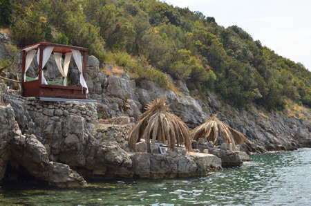 Straw parasols and cabana bed on beach rocks with green sea water in summer