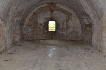 Prison cell with a window covered with bars in an abandoned old fortress