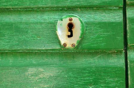 Close-up of a door lock in vintage style on a green wooden door