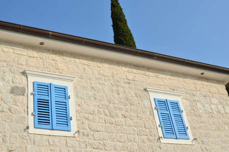 Two windows with blue wooden jalousies on a coastal house facade
