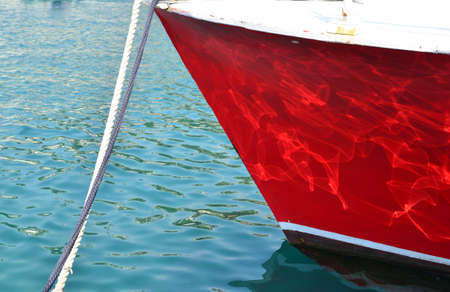 Bow of a moored red boat in a blue sea