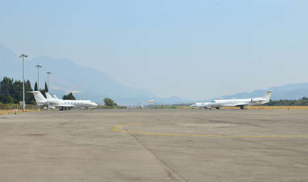 Two airplanes parked on an empty runway with a landscape in a background Imagens