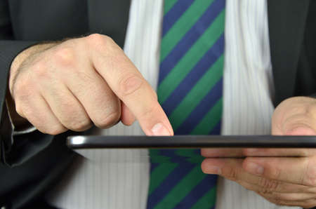 Businessman is holding and using a tablet with a touchscreen