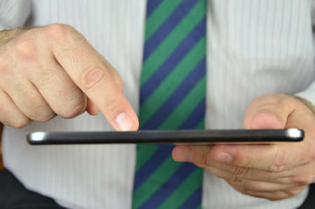 Businessman is using a tablet with a touchscreen