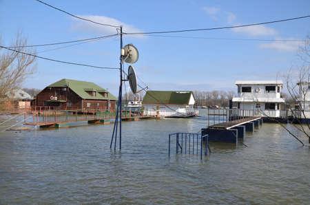 Flood over a promenade along a river bank in a city area Stock Photo