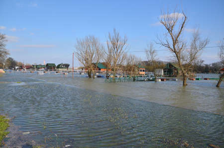 Flooded promenade along a river bank in a city area Stock Photo