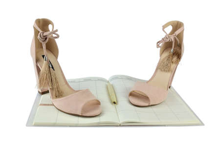 Nude look Roman style high-heeled sandals on an open planner - white background Stock Photo