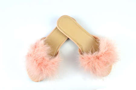 Flat pink feather slippers in a crossed position