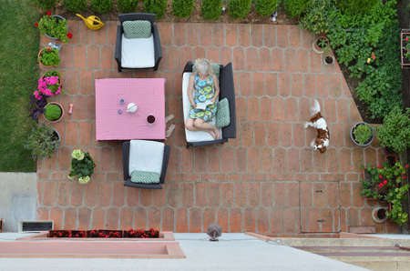 Woman and dog relaxing in a garden shot from above - bird's-eye view