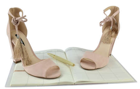 Nude look Roman style high-heeled sandals on an open planner with a pen - white background