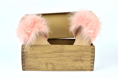 Pink feather slippers in a cardboard box with wooden pattern Stock Photo