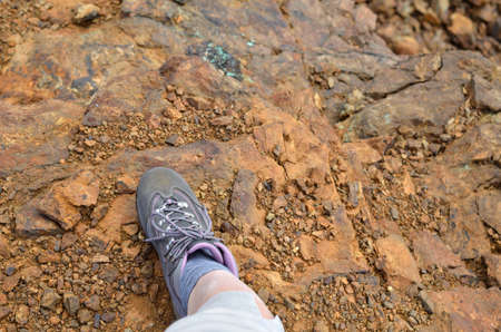 Top view of a foot in hiking shoe on a surface of orange dirt and stones Banque d'images