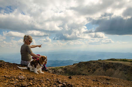 Woman and her dog, Cavalier King Charles Spaniel, are watching picturesque mountain landscape