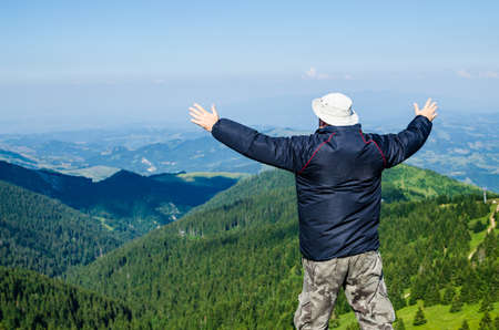 Man with spread arms in a joyful pose, in a mountain landscape