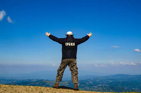 Man with spread arms in a joyful pose, on a mountain top, watching idyllic landscape of the mountain. Translation of the text on the jacket: