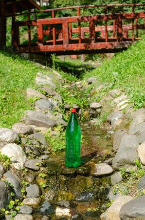 Green plastic bottle of mineral water in a stream Reklamní fotografie