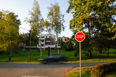 Stop sign with a black car in motion on a street behind in the daytime Foto de archivo