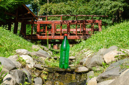 Green plastic bottle of water in a stream with a small wooden bridge behind