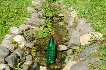 Green plastic bottle of water in a brook on a sunny day 写真素材