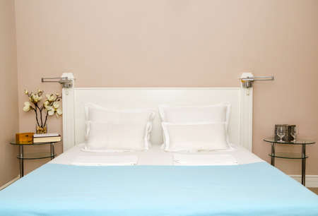 Double bed with pillows, sheets and blanket in a bedroom - close-up 写真素材