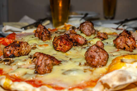 Served pizza with meat and cheese - close-up