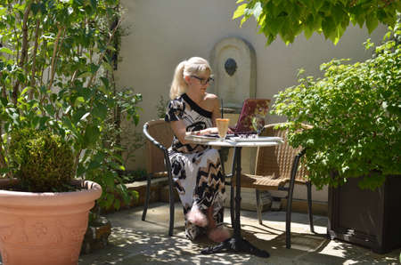 Business woman on holidays casually but elegantly dressed working on a laptop