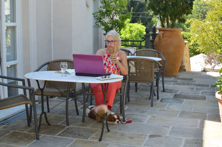 Woman on vacation casually but elegantly dressed working on a laptop and drinking coffee