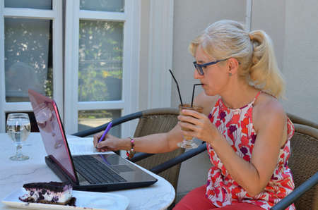 Woman working with technology outside an office and drinking coffee