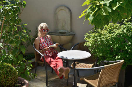 Woman elegantly dressed reading and relaxing in a garden 写真素材