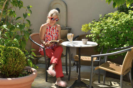 Woman elegantly dressed reading and drinking coffee in a garden