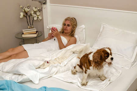 Blonde woman relaxing on a bed with her dog and using cell phone 写真素材