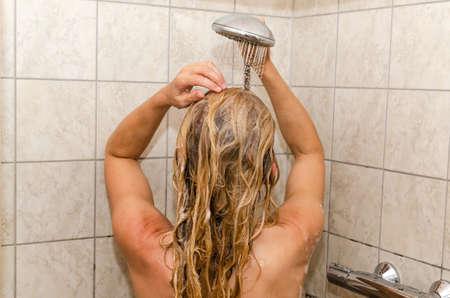 Blonde woman taking a shower in a cabin