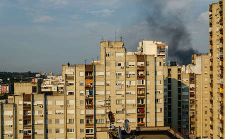 Black smoke of a fire above buildings in a residential part of a city Stock Photo
