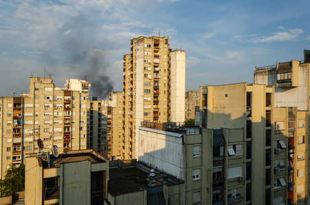 Black smoke of a fire above buildings in a residential part of a city 写真素材