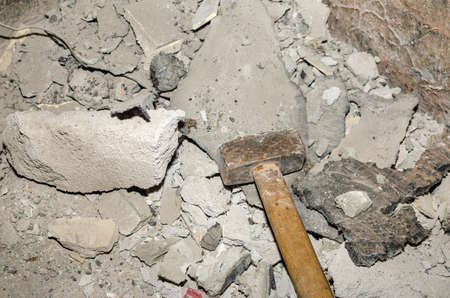 Hammer and parts of plaster after wall destruction works